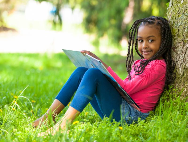 African American Child reading book by, for and about Black people